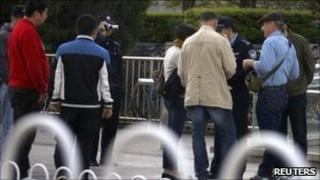 Plainclothes police watch as uniformed policemen question CNN reporter Stan Grant (C) and colleagues, Beijing April 24, 2011