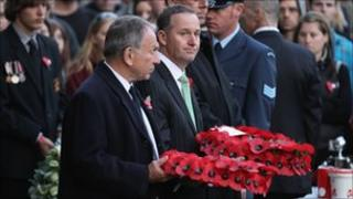 New Zealand Prime Minister John Key (centre) holds a wreath at the Australian War Memorial
