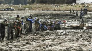 Japanese soldiers search for the bodies of people missing since the 11 March earthquake in Shichigahamamachi, Miyagi Prefecture, northeastern Japan, on Monday