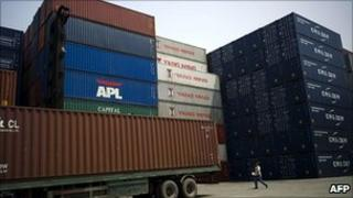 A Chinese lorry driver walks past containers in Shanghai, 25 April 2011