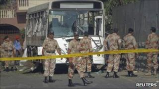 Paramilitary soldiers arrive at the scene after a bus carrying Pakistan Navy officials is hit by a bomb in Karachi on 26 April 2011