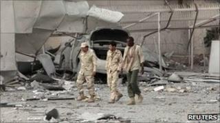 Libyan soldiers walk through ruins in Tripoli