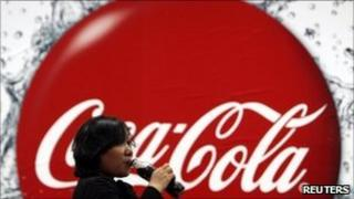 Woman drinking a bottle of Coca Cola in front of the company's logo