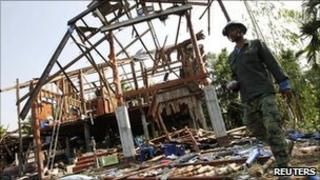 A Thai man walks past a destroyed house in Karb Cherng village in Surin province on 27 April 2011