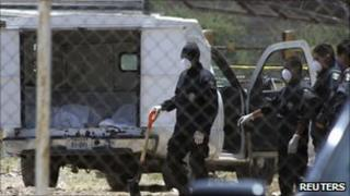 Federal police work to exhume bodies from the graves in Durango on 20 April 2011
