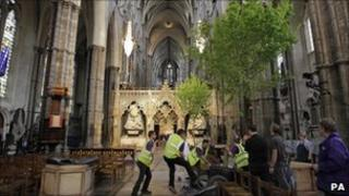 Workers carry an English field maple tree into Westminster Abbey in preparation for the royal wedding