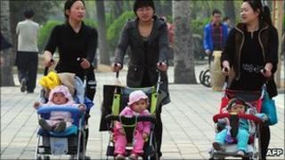 Women push babies in prams through a Beijing park (5 April 2011)