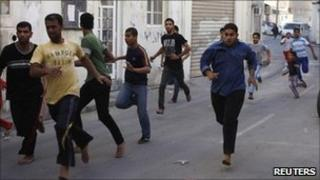 Bahraini men flee during a protest as riot police enter their village of Dai, east of Manama, on 24 March