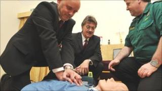 Two men practicing CPR on a dummy