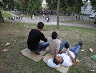 Tunisian migrants sit in a Paris square, 26 April
