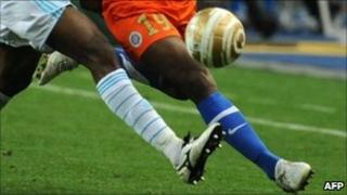 Two black footballers chase the ball at the Marseille-Montpellier French League Cup final in Paris, 23 April