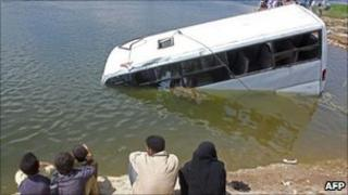 Egyptians look at a sunken minibus in the Nile river in Beni Suef, Egypt, 29 April 2011.