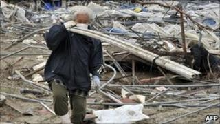 An elderly woman salvages scrap metal in a ruined area of Sendai on 28 April 2011