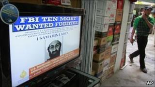 An Afghan youth walks past a television announcing the death of Osama Bin Laden