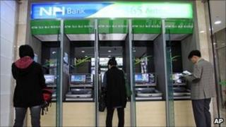 Customers use cash machines at a Nonghyup bank on 3 May 2011
