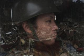 A Japanese Self Defence Force soldier looks out of a window at the devastation in Rikuzen-Takaata, Iwate Prefecture