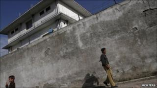 A policeman walks in front of the compound where al Qaeda leader Osama bin Laden was killed in Abbottabad May 3, 2011