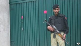 A Pakistani policeman stands guard at the Bin Laden compound in Abbottabad