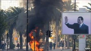 Smoke rises from fire left after clashes between security forces and demonstrators in Tunis on 14 January 2011 after Tunisian President Zine al-Abidine Ben Ali's resignation