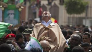 In this photo made on a government organised tour, a supporter reacts during funeral ceremony for members Gaddafi family in Tripoli, Libya, Monday 2 May 2011