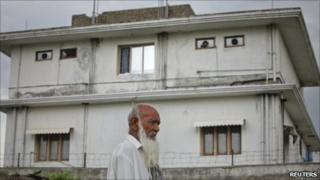 A resident walks past the compound where US commandoes killed Bin Laden. Photo: 5 May 2011