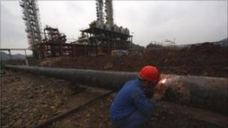 Welding a pipe at oil refinery in China