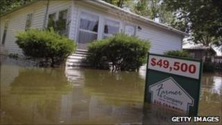 A realtor sign sitting in front of a flooded home in Illinois