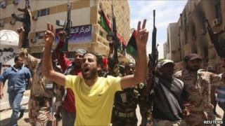 Rebel fighters attend funeral of a comrade in Benghazi on 7 May 2011