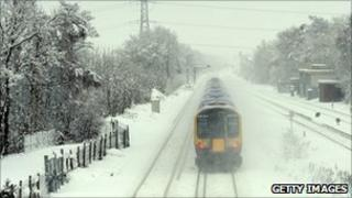 A train runs through the snow in Winchfield, Hampshire