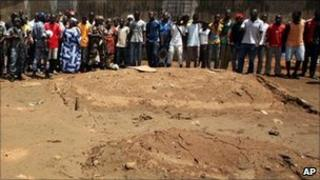Residents look on as soldiers visit the site of an alleged mass grave in Yopougon district, Abidjan, on 5 May 2011
