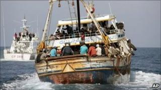 Boat overloaded with North African migrants is escorted into Lampedusa harbour, Italy (19 April 2011)