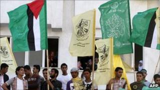 Palestinian students carry the flags of the Hamas movement (green) and the Fatah party (yellow) to mark the unity deal, Gaza City (8 May 2011)