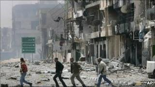 Residents run through damaged streets in Misrata, Libya (23 April 2011)