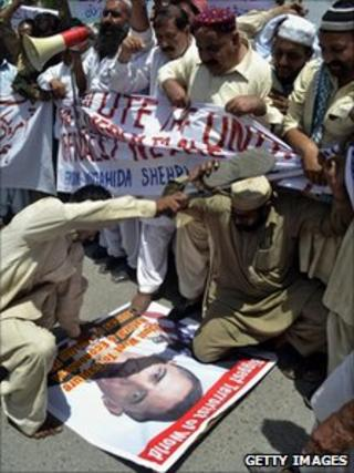 Pakistani protesters beating a poster of US President Barack Obama
