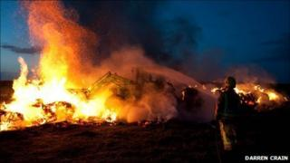A tractor is used to help tackle the fire