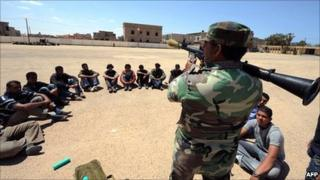 Libyan youths listen to instructions from a rebel on how to use a Rocket Propelled Grenade (RPG) during the final phase of their military training in the eastern city of Benghazi on 9 May 2011