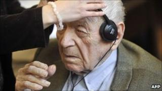 An official helps Sandor Kepiro with headphones at court in Budapest, Hungary (10 May 2011)