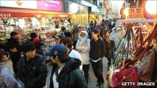 South Koreans walk through a shopping district in Seoul.