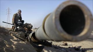 Rebel fighter sits on destroyed tank