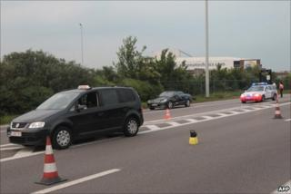A police car stands behind the taxi involved in the shooting at Brussels airport, 11 May