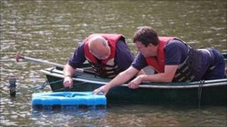 Rangers Roland Mackie and Ray Bicknell installing the aerator
