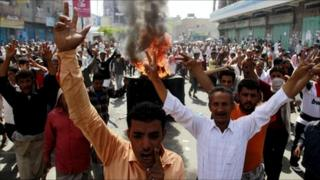 Anti-government protesters march near burning tyres in the southern city of Taiz, 11 May 2011
