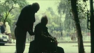 Carer pushing man in wheelchair