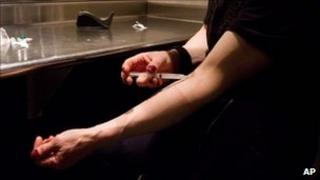 A person injecting morphine at Insite