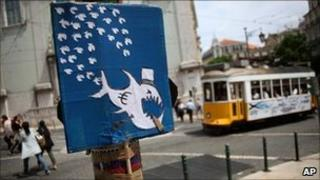 A placard in Lisbon, Portugal, caricatures the euro as a big fish devouring minnows, 5 May