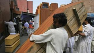 Men bring coffins to a hospital morgue in Peshawar, for the victims of a suicide bomb blast in Charsadda May 13, 2011.
