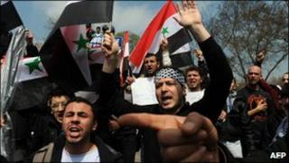Protesters hold Syrian flags