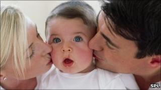 Father and mother kissing baby
