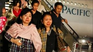 Passengers leave a Cathay Pacific flight after it made an emergency landing in Singapore