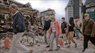 People walk through debris in the aftermath of a 6.3 magnitude earthquake in Christchurch, New Zealand, on February 22, 2011